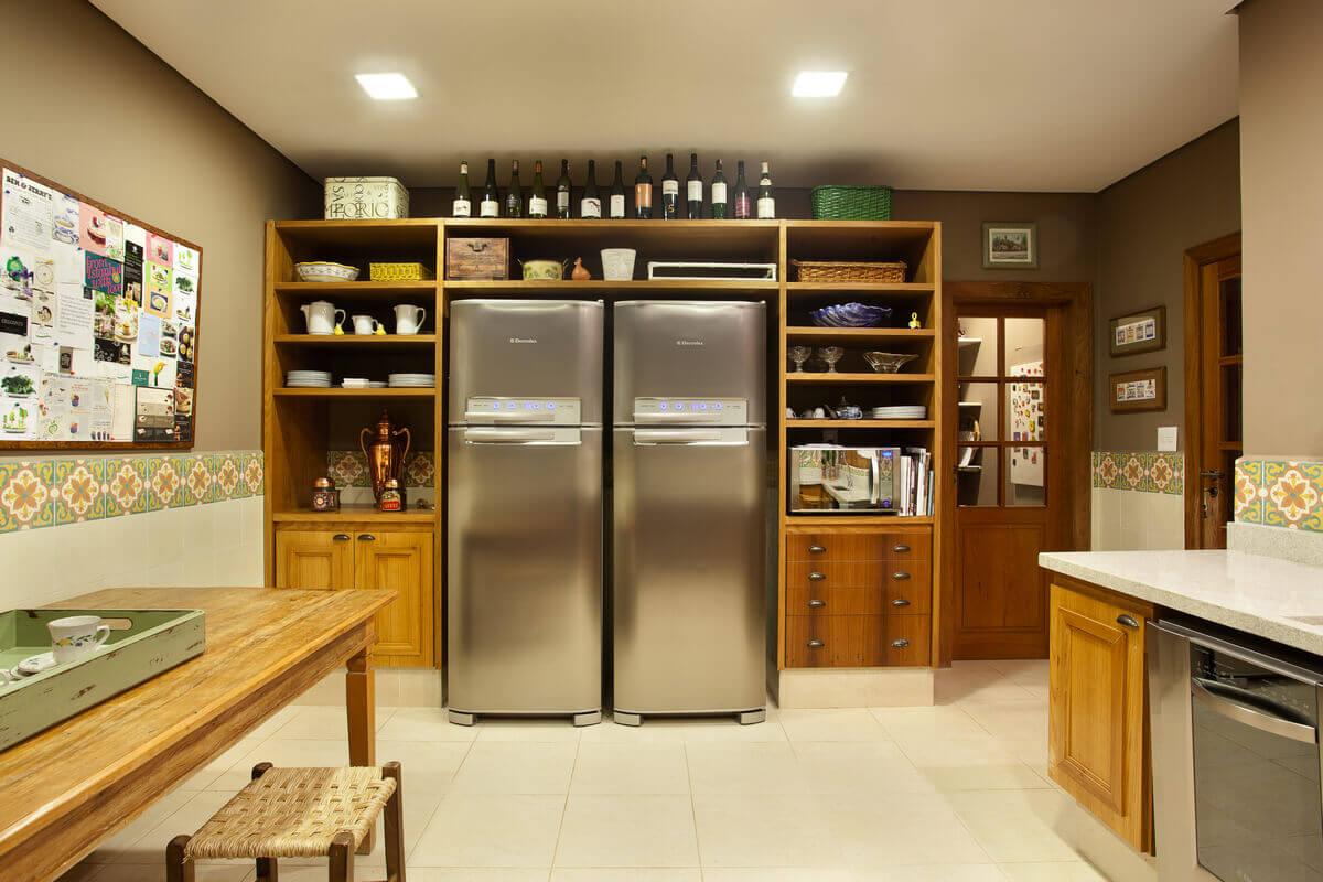 Cozinha rústica com nichos abertos em torno das geladeiras.