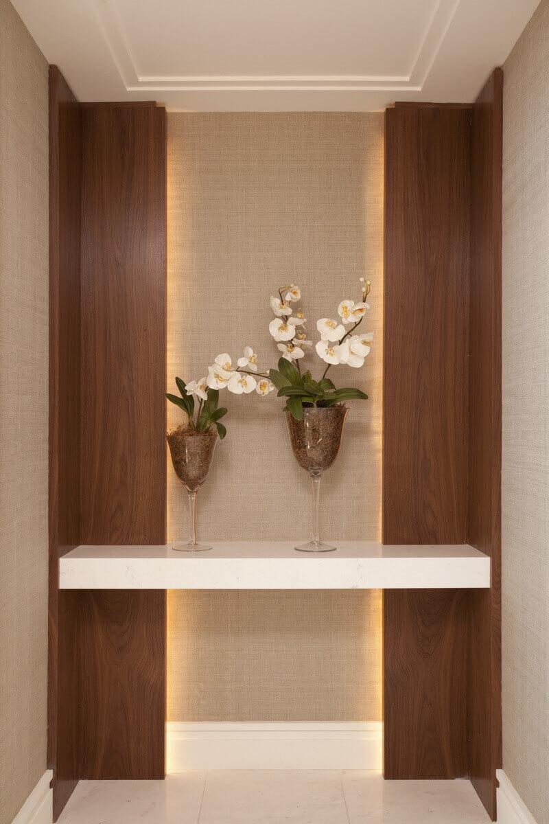 Hall do elevador com piso e tampo em mármore branco, painéis de Nogueira com iluminação indireta e paredes revestidas em palha de seda da Nani Chinelatto.