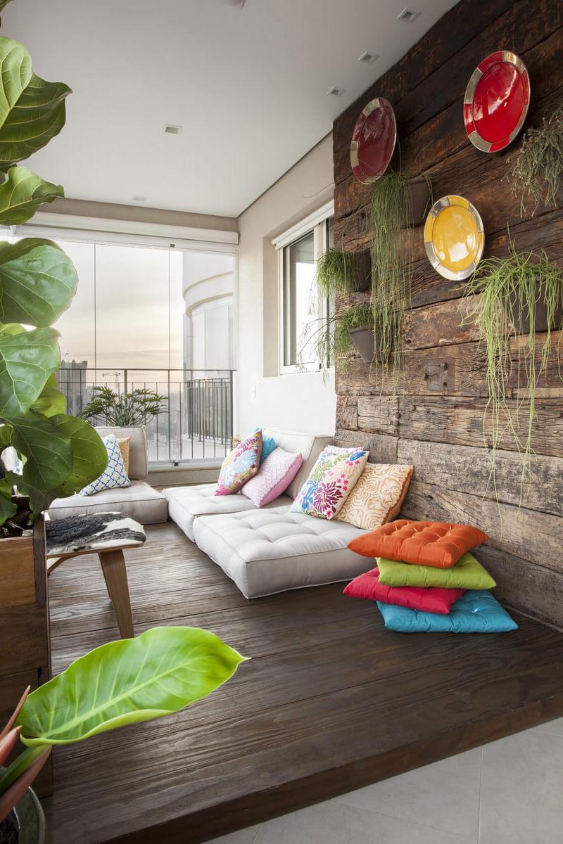 Painel de madeira de demolição com arranjos de pratos e vasos de plantas. Deck de madeira com futons, o canto preferido dos adolescentes.