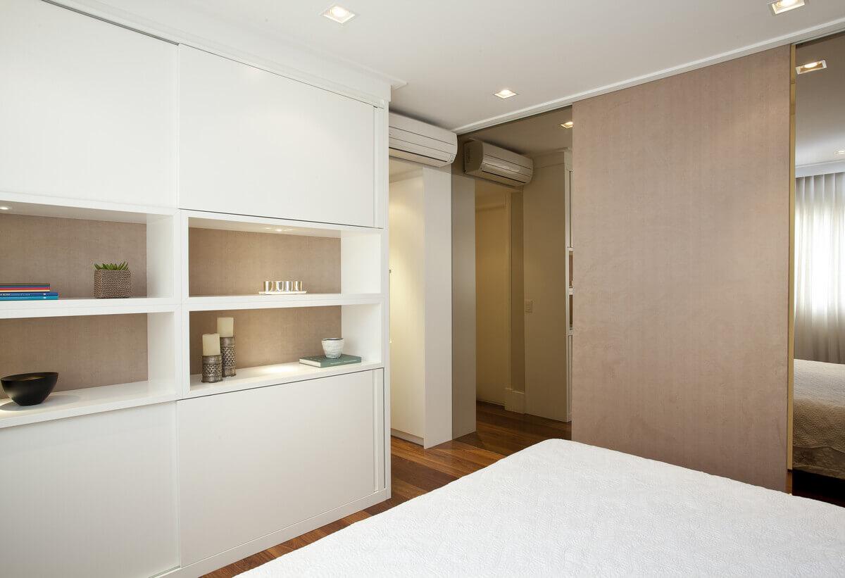Para dar leveza, os armários na frente da cama possuem nichos revestidos em camurça. Separando o quarto do closet, a porta de correr em camurça corre sobre os espelhos bronze.