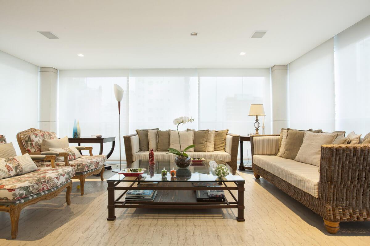 Varanda com piso de travertino. Ambiente com móveis de vime e mesa de centro de bambu e vidro.