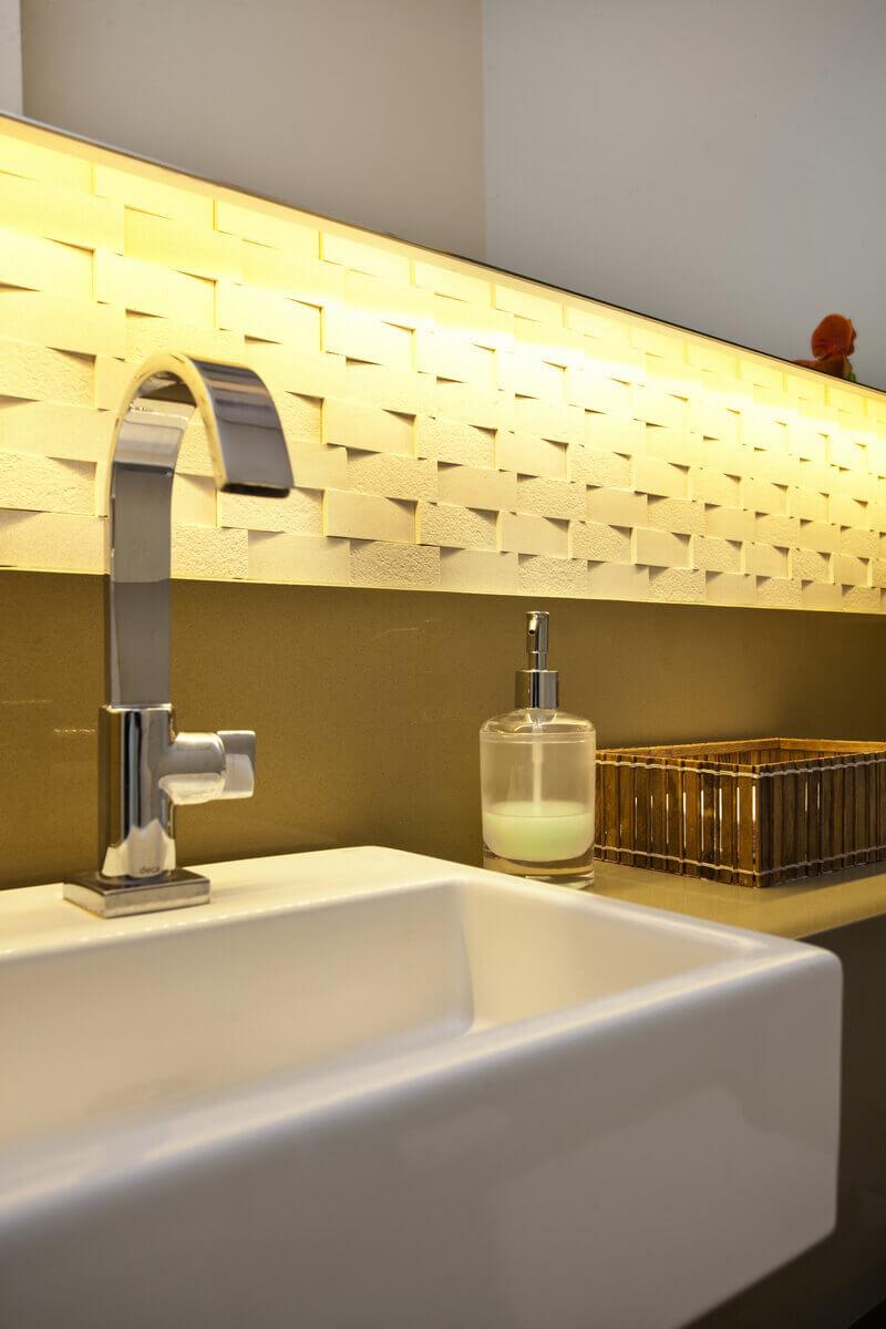 Detalhe do realce da volumetria do revestimento cimentício, dado pela fita de LED por trás do espelho.
