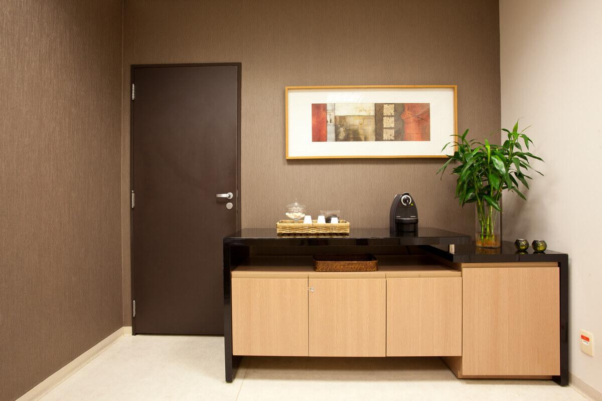 Bancada de apoio para café na recepção. Papel de parede marrom da Orlean.