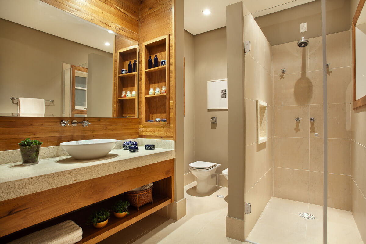 Banheiro da suíte master. Painel e nichos de madeira de demolição e bancas de limestone Golden Oasis, em contraste com porcelanato bege.