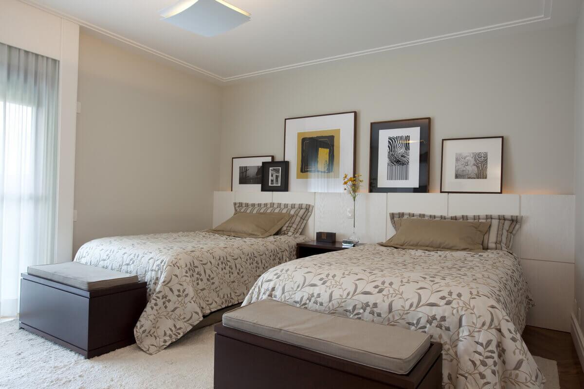 Na suíte master, a cabeceira de couro branco une as duas camas de casal e serve de suporte para os quadros e gravuras.
