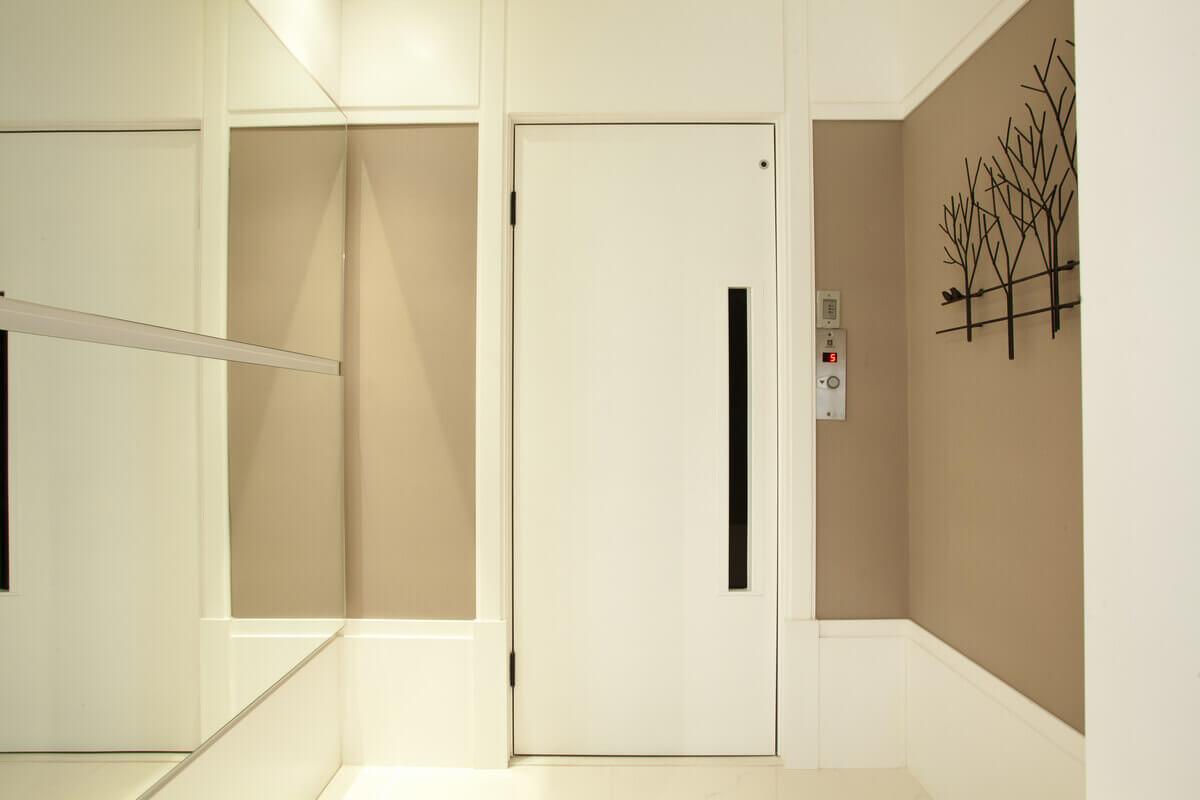 Hall de elevador, com o espelho escondendo o quadro de luz, formando um jogo com o roda teto e o rodapé.