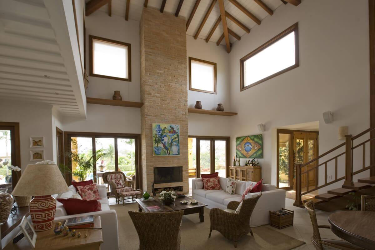 Sala de estar com destaque para lareira em tijolos de demolição e o pé direito duplo. As janelas do alto compõe a fachada e iluminam a sala.
