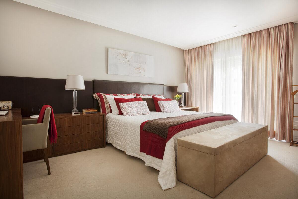 Suíte de casal com cabeceira estofada em couro com fita de LED. Criados e escrivaninha em Nogueira, predominando o marrom, vermelho e branco.