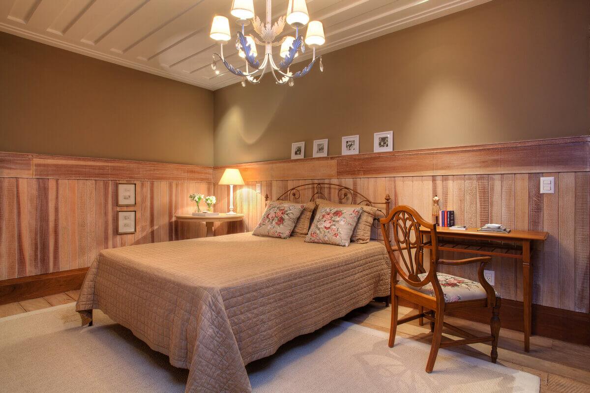 Quarto com paredes revestidas com lambri de madeira de demolição, em contraste com móveis de estilo clássico.