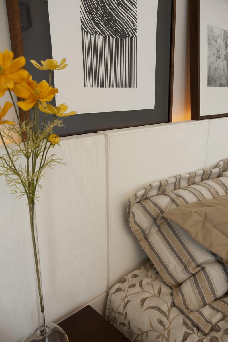 Detalhe da cabeceira de madeira branca com partes revestidas em couro e iluminação com fita de LED.