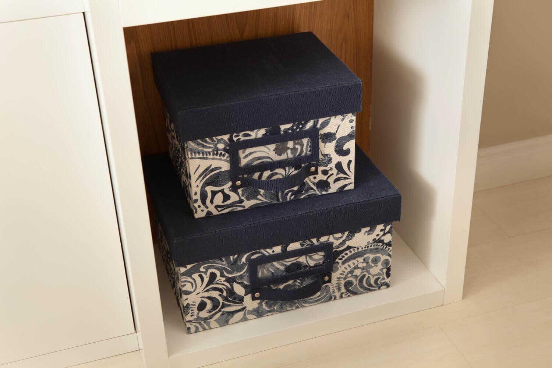 Caixas revestidas em tecido do Cecilia Nucci Ateliê em estante de marcenaria de laca branca.