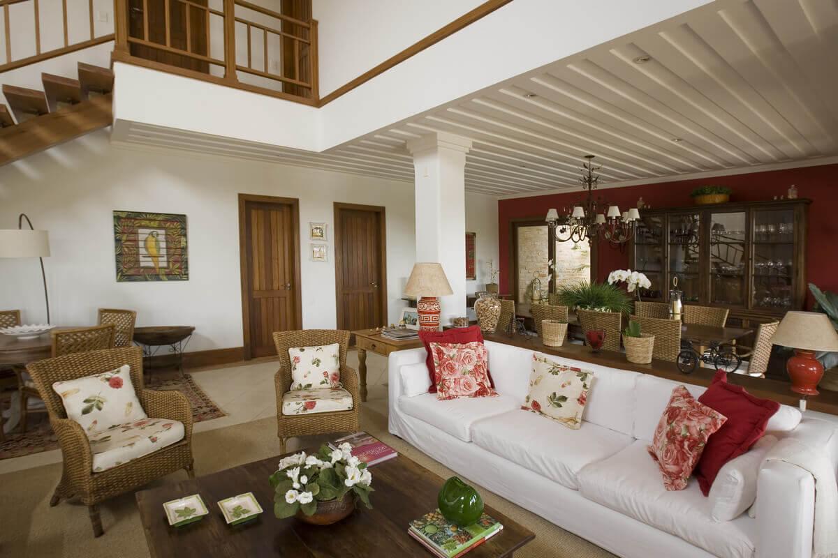 Sala de estar com sala de jantar ao fundo com parede vermelha. Forro de gesso saia e blusa e escada com guarda-corpo em madeira.