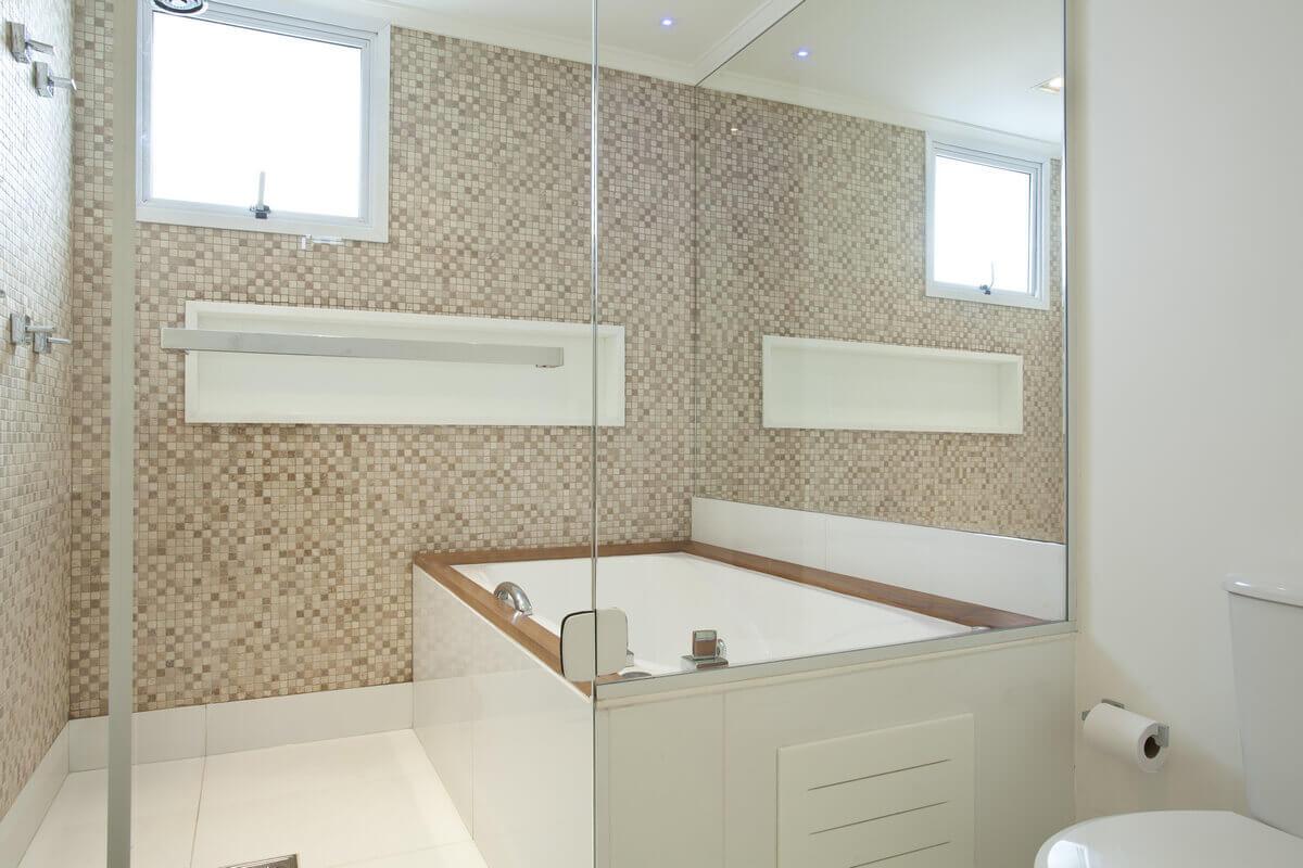 Banheiro com banheira com paredes revestidas de pastilhas de mármore da Mosarte, com nicho em marmoglass.