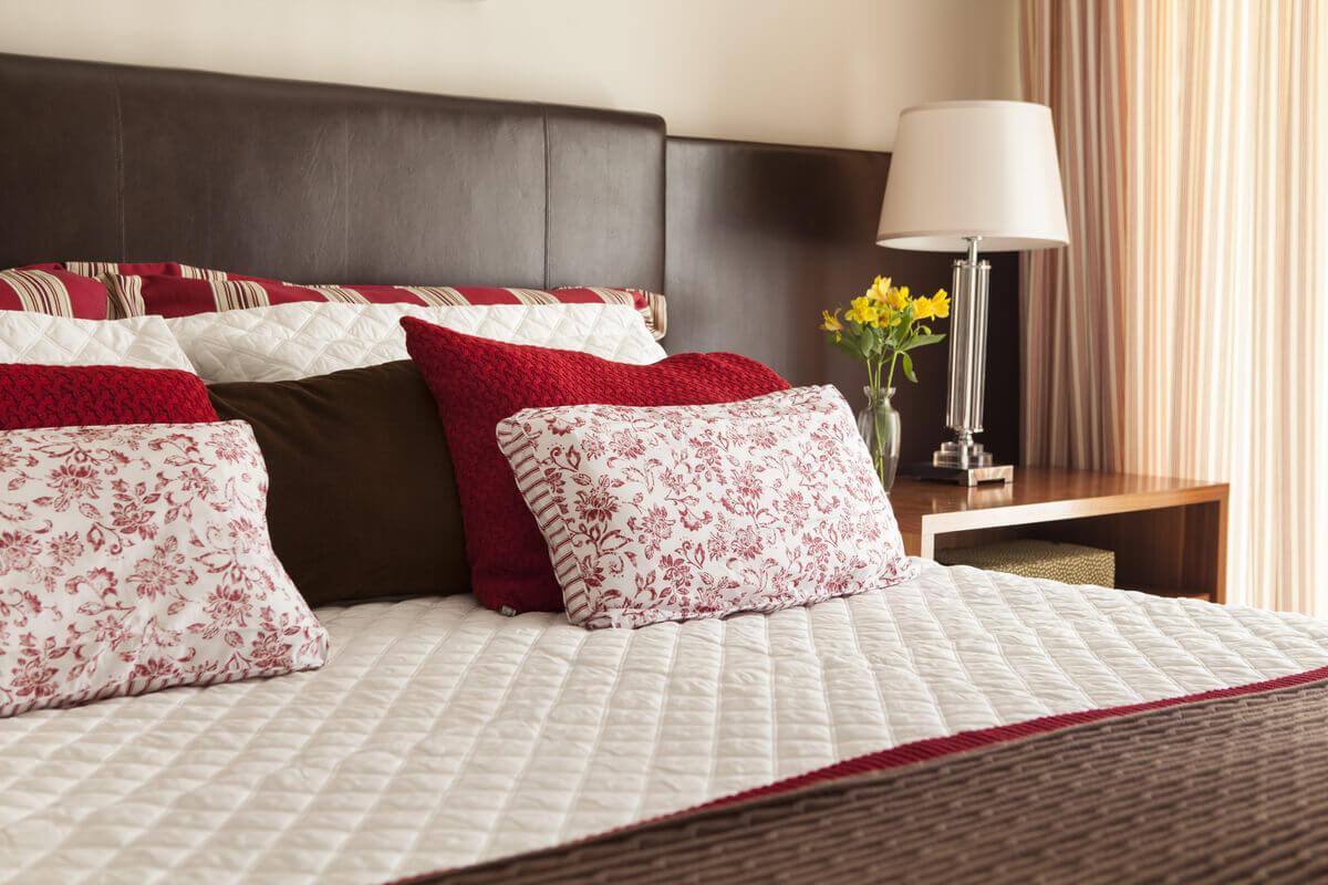 Detalhe de porta travesseiro em tricô vermelho e tecidos estampados, realçando o fundo marrom e branco.
