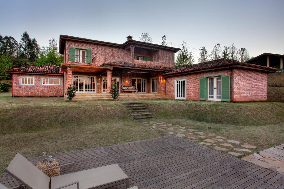Casa com arquitetura Toscana. Tijolos rústicos e caixilhos de madeira pintados de verde e branco.