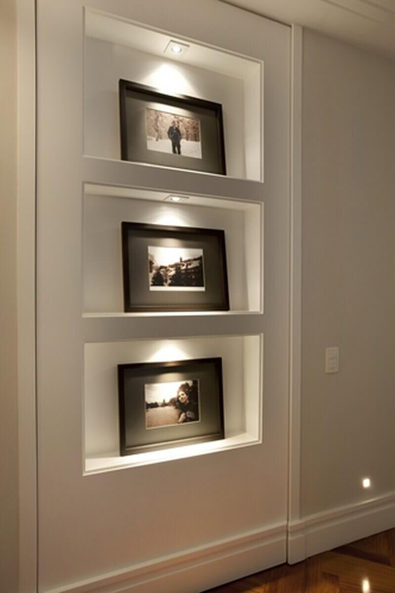 Esta estante embutida na parede com nichos para fotografias, é também uma porta para um quarto secreto.