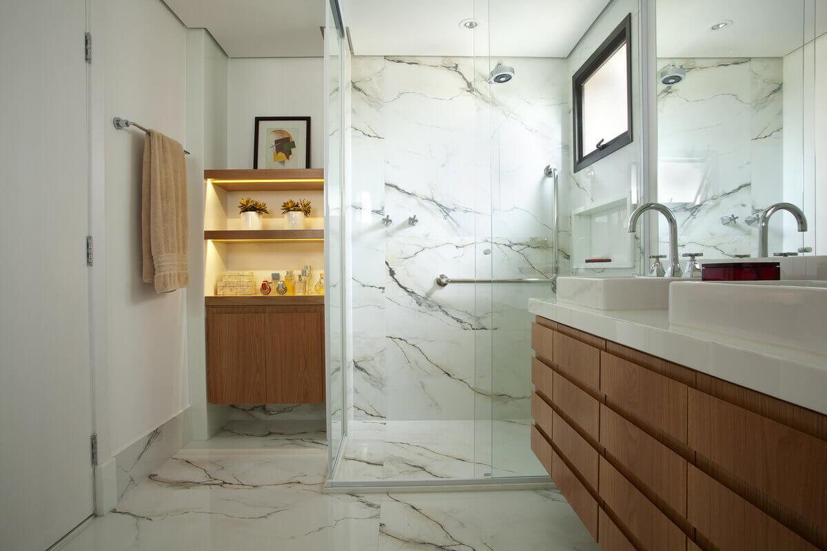 Box de banheiro e piso revestidos em porcelanato Portobello Paonazzetto. Nichos em freijó iluminados com fita de LED.