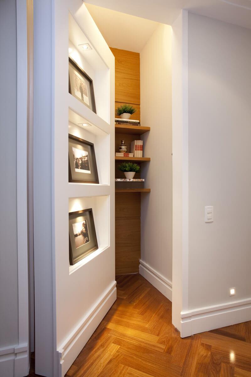 Estante pivotante com nichos iluminados para fotografias e porta de um depósito secreto.