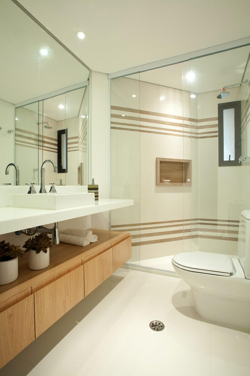 Banheiro com gabinete em freijó lavado. Box com porcelanato Araucaria Clara da Portobello, nas faixas e no nicho.