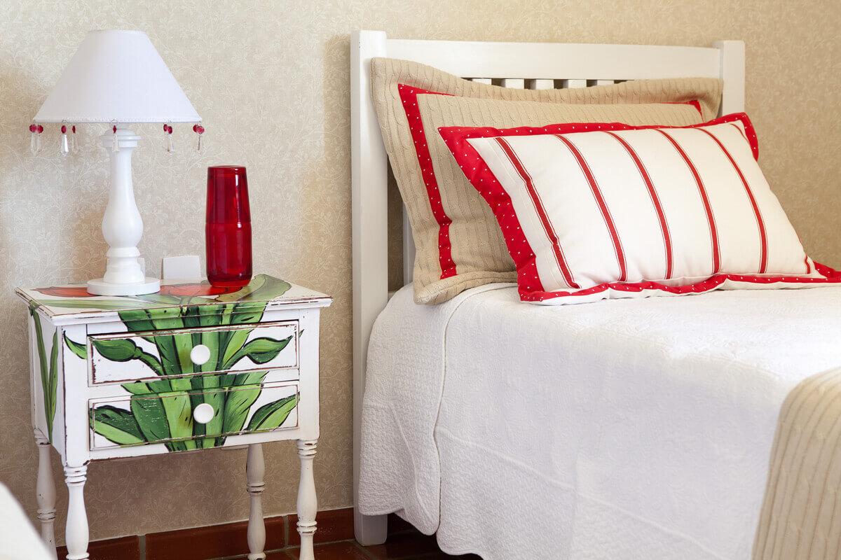 Detalhe para porta travesseiros com detalhes em vermelho e criado-mudo com pintura artesanal.
