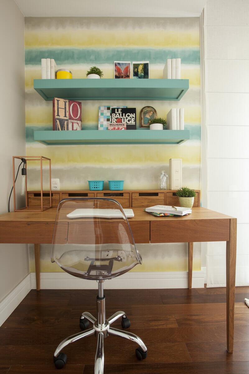 Canto da escrivaninha na suíte com papel de parede listrado. Detalhe para a cor azul tiffany que aparece também nas prateleiras.