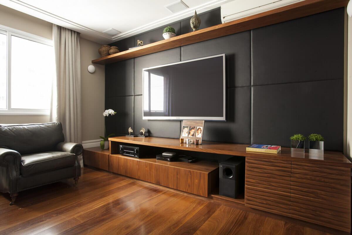 Home theater moderno com painel de couro preto e marcenaria em Nogueira com ripas horizontais.