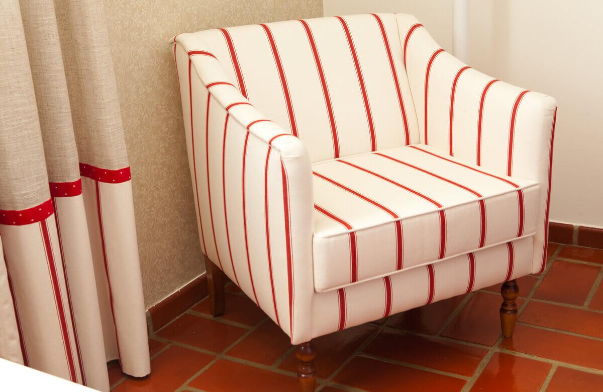 Detalhe da barra da cortina combinando com tecido da poltrona e papel de parede bege.