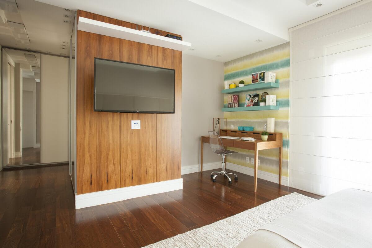 Integração da suíte master com painel de madeira para televisão.