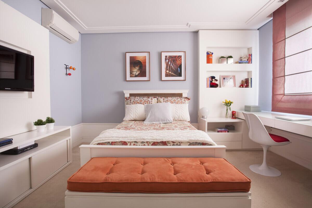 Quarto feminino em tons de laranja com nichos, bancada e cama em laca branca. Cortina romana.