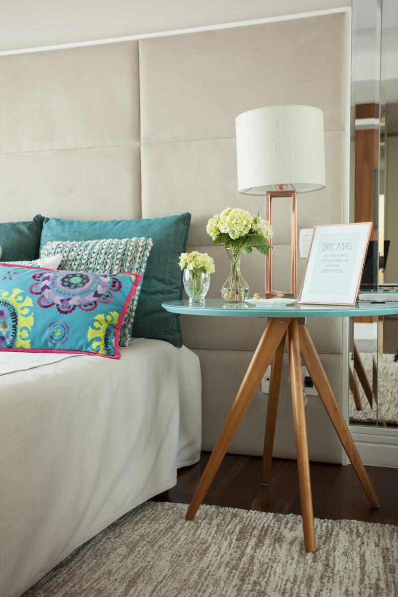 Mesinha de cabeceira com pés palito e tampo azul tiffany. As almofadas estampadas ganham destacam sobre a cabeceira estofada.