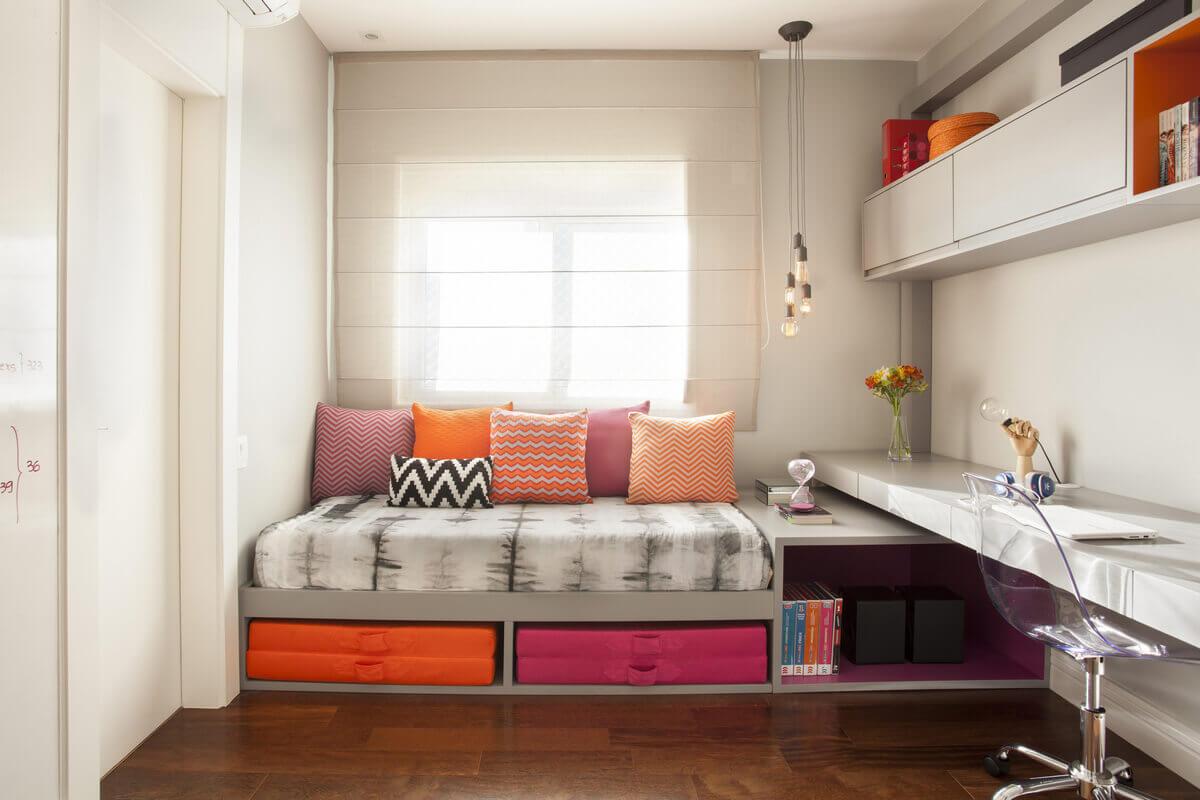 Quarto feminino, em tons de cinza, iluminando-se com detalhes nas cores laranja e rosa.