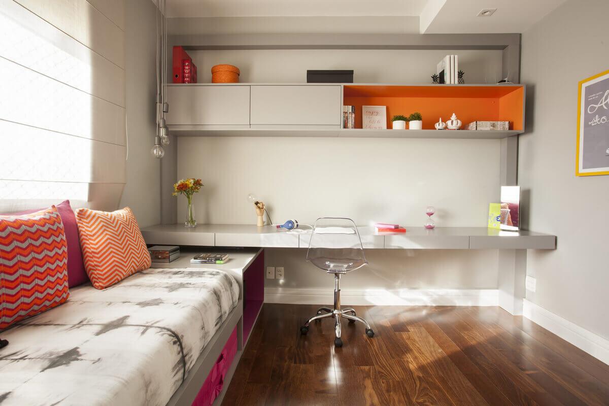 Colcha da Tie Dye com almofadas de tricô nas cores laranja e rosa. Armário suspenso com nicho laranja, realçando os objetos.