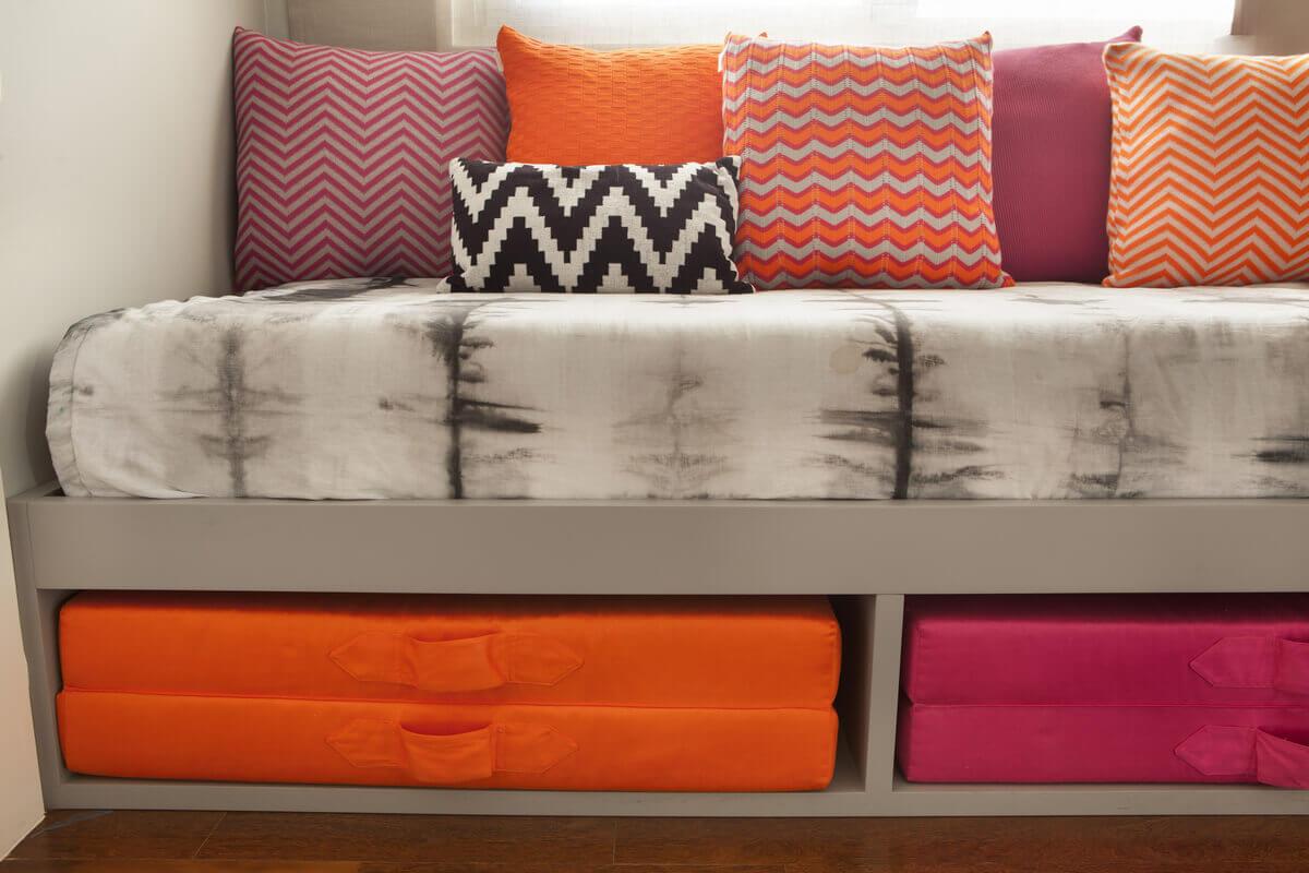 Os tons sóbrios da parede e da colcha ganham vida com as almofadas divertidas em tricô da Macadamia Home.