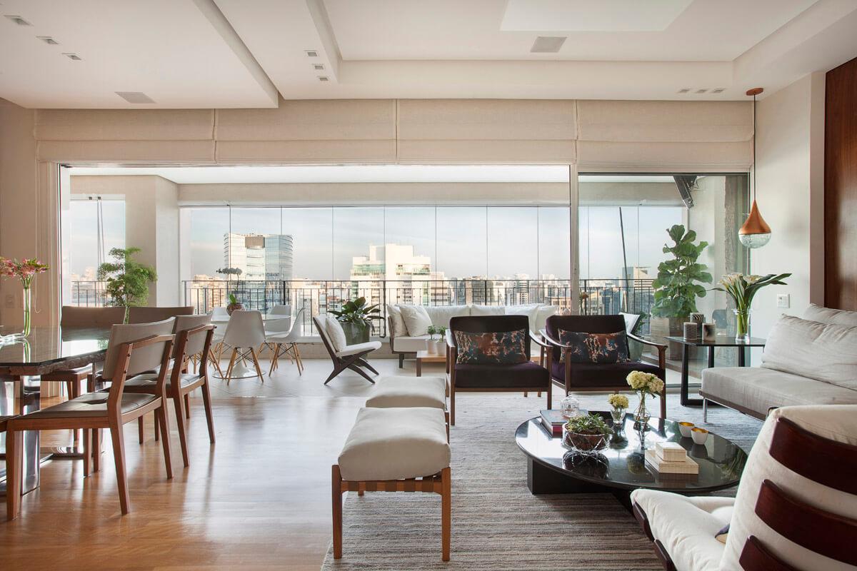 Salas integradas, varanda, living e jantar com skyline ao fundo