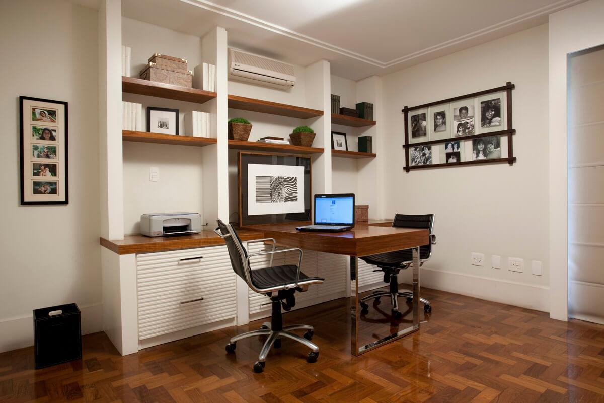 Home office com escrivaninha engastada na estante em laca e nogueira ripada