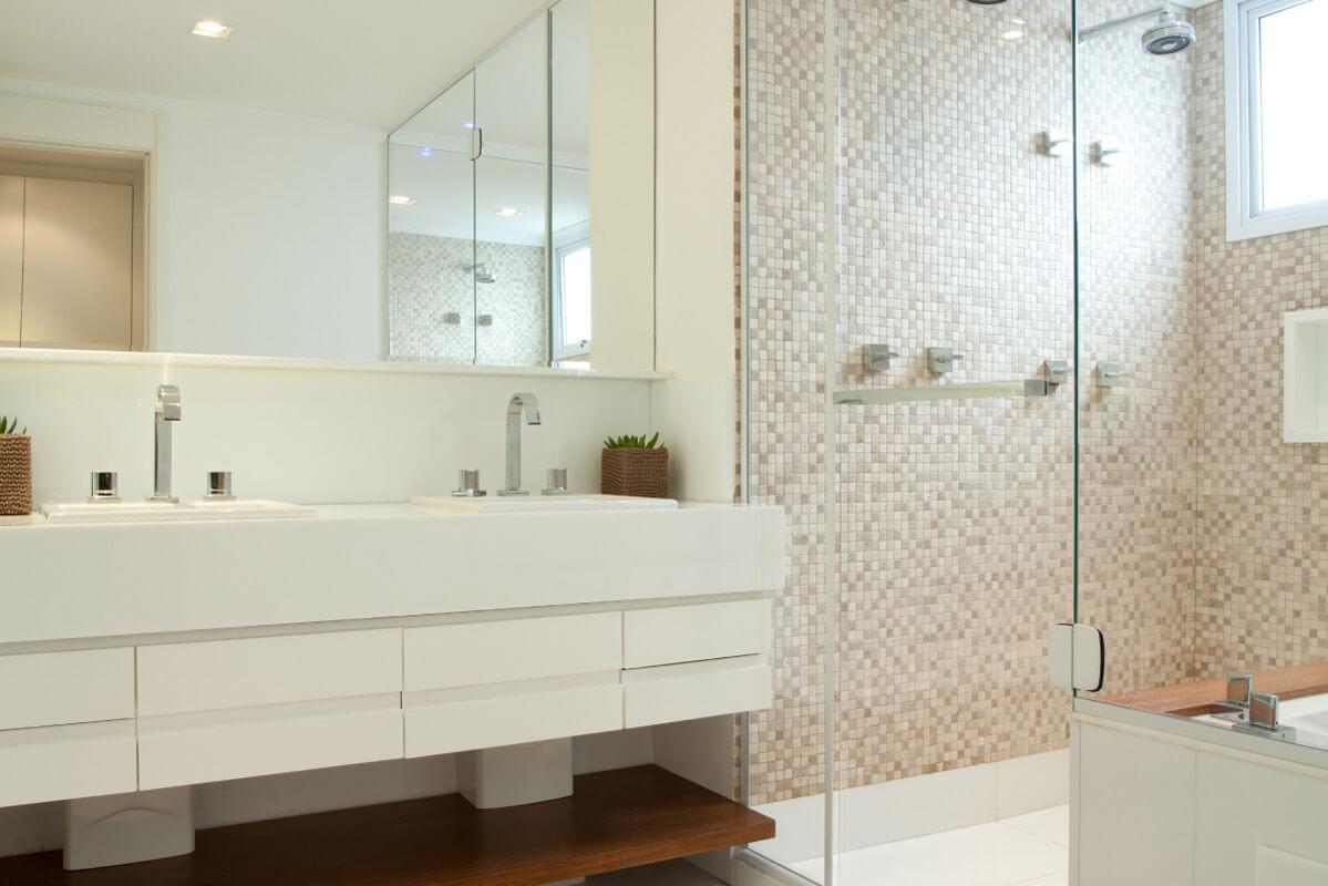 No banheiro da suíte master, o box revestido em pastilhas de mármore da Mosarte destaca-se do piso. A prateleira em freijó aquece o ambiente.