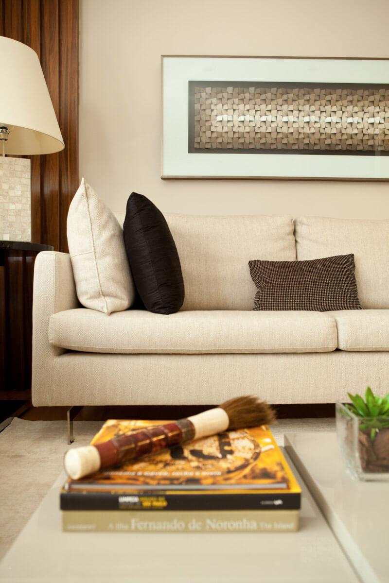 No detalhe do living, destaque para tela sobre o sofá e para a mesa de centro de vários níveis da Artefacto.