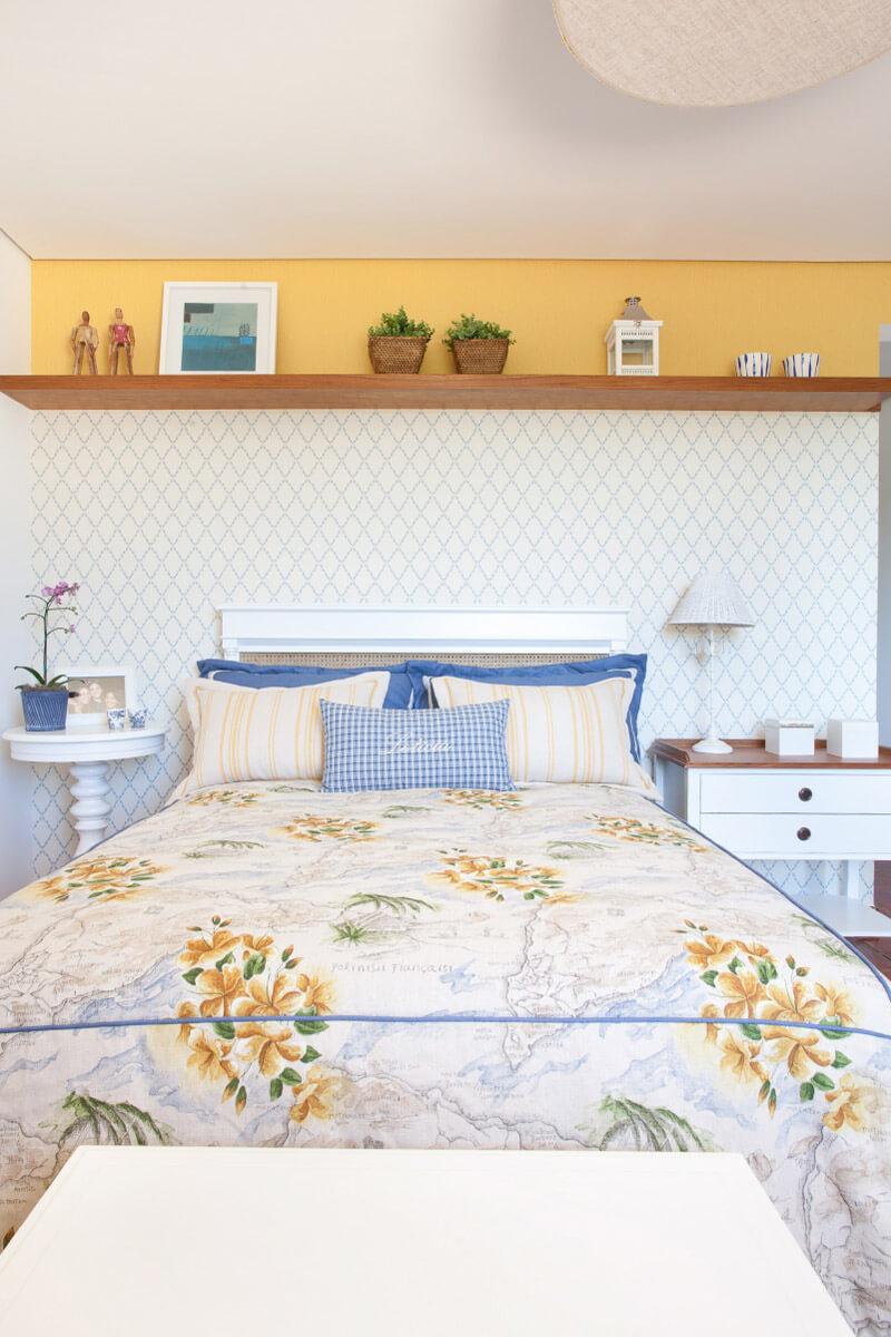Colcha e porta travesseiros em tecidos da Entreposto. Cabeceira revestida com papéis de parede separados por prateleira decorativa.