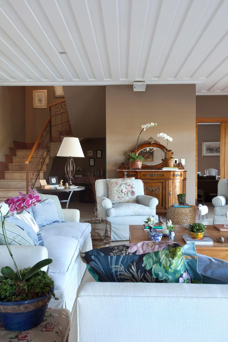 Sala de estar com móvel antigo ao fundo. Escada com guarda-corpo em ferro e corrimão em Pinho de Riga, desenhados pela arquiteta.