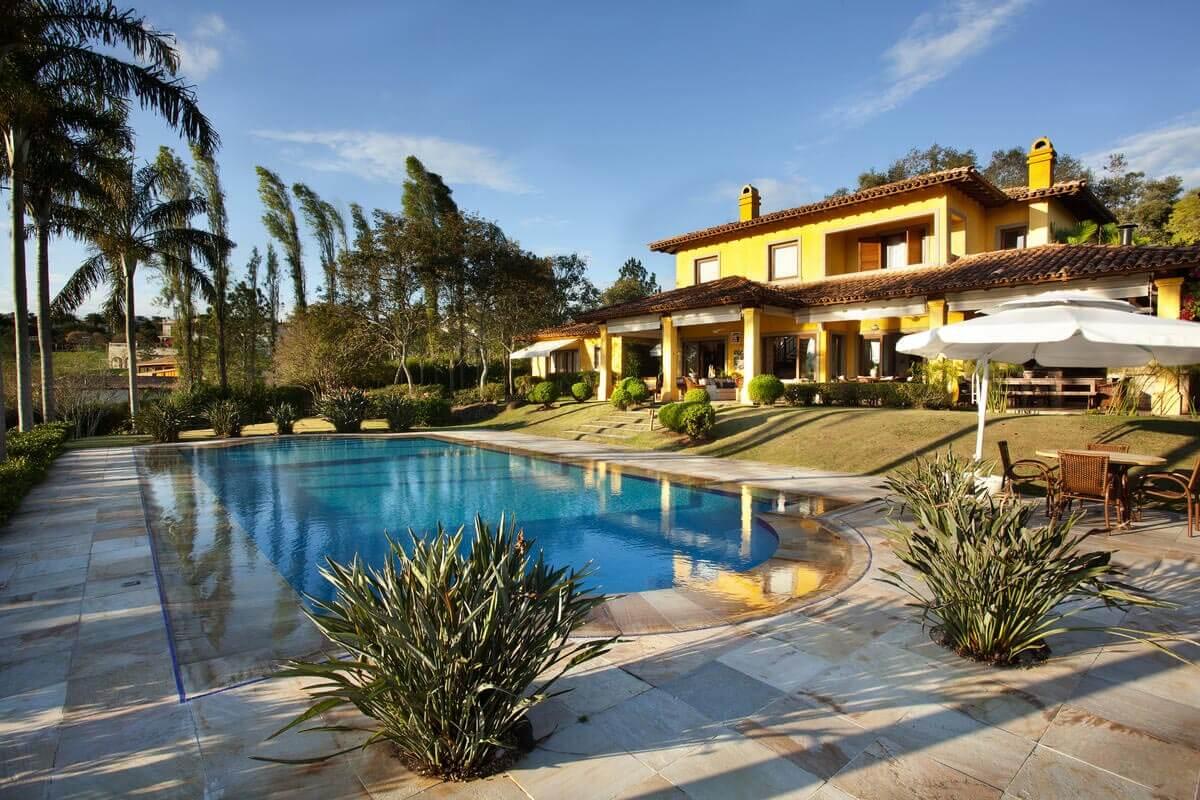 Casa na Quinta da Baroneza - vista da piscina com deck de pedra mineira e jogos de telhado