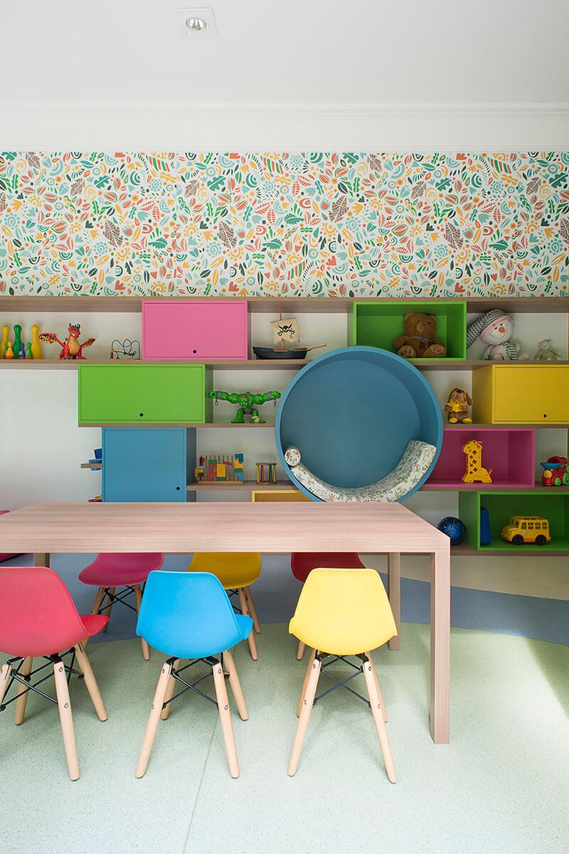 brinquedoteca com  marcenaria colorida e nichos abertos e fechados , papel de parede e piso vinílico organico