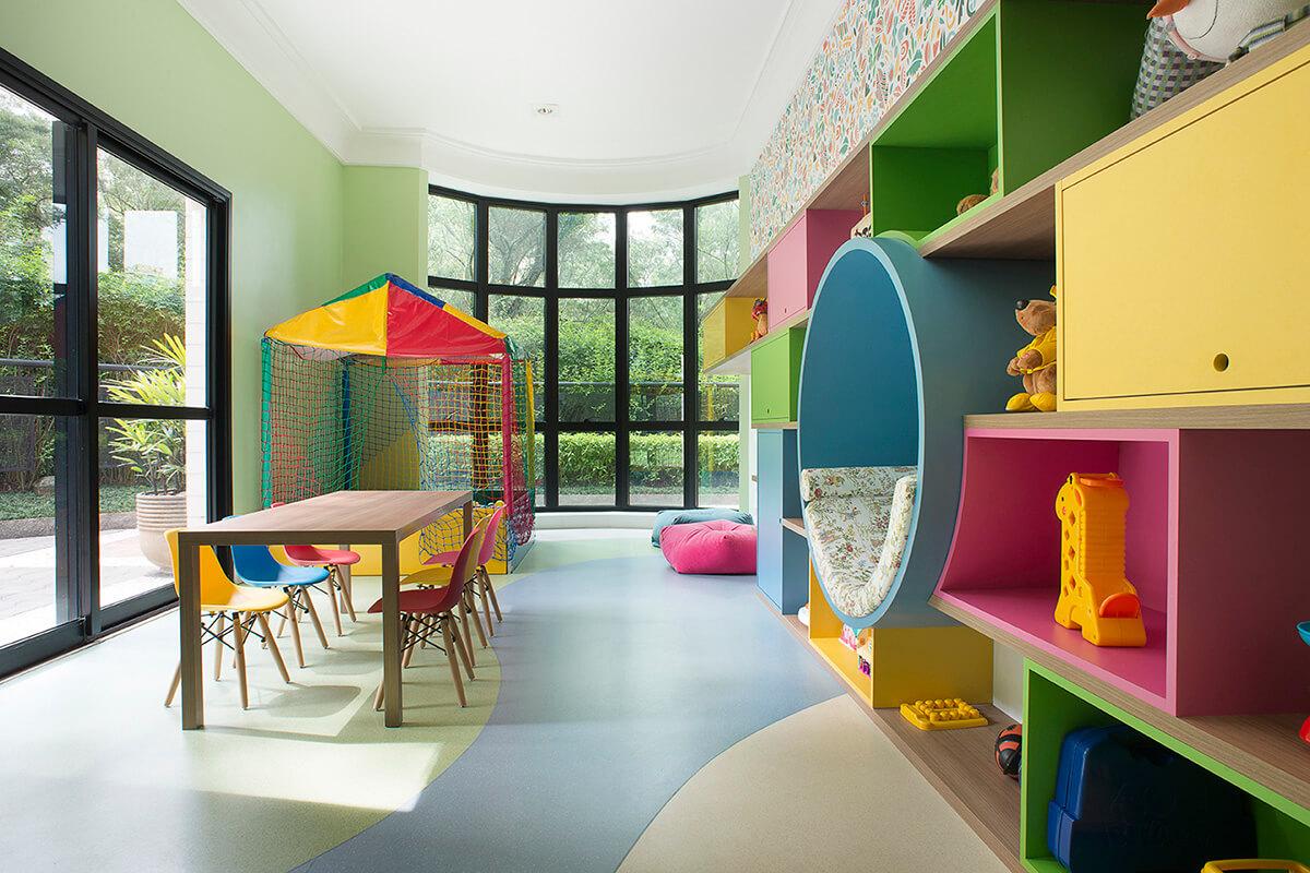 brinquedoteca colorida com nichos abertos e fechados, espaço para leitura, estante para livros, piso vinílico com desenho orgânico