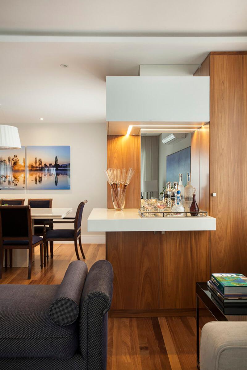 sala integrada em tons de azul e terra, com bar em madeira, espelho e vidro branco