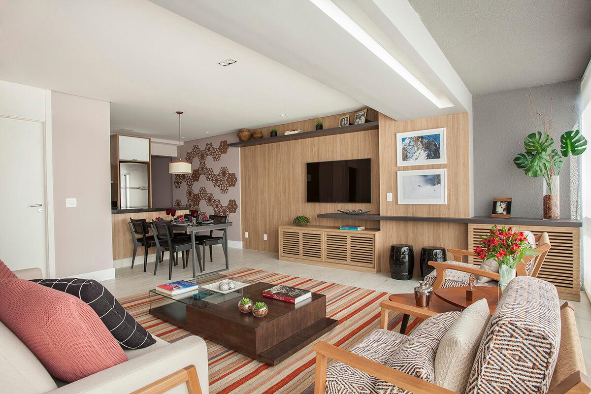 sala, varanda e cozinhas integrados em apartemento pequeno com tapete listrado e painel de madeira