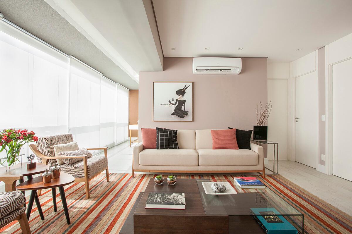 living com parede Rose com quadro colocado fora do centro, tapete listrado e sofas e poltronas com braços em madeira