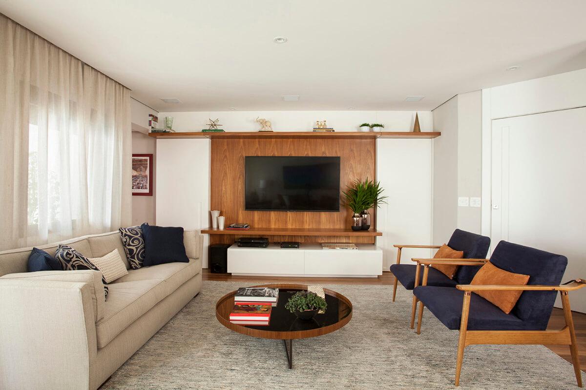 sala em tons de azul e terra,painel em madeira e portas que ocultam a passagem para o área íntima da casa e a cristaleira.