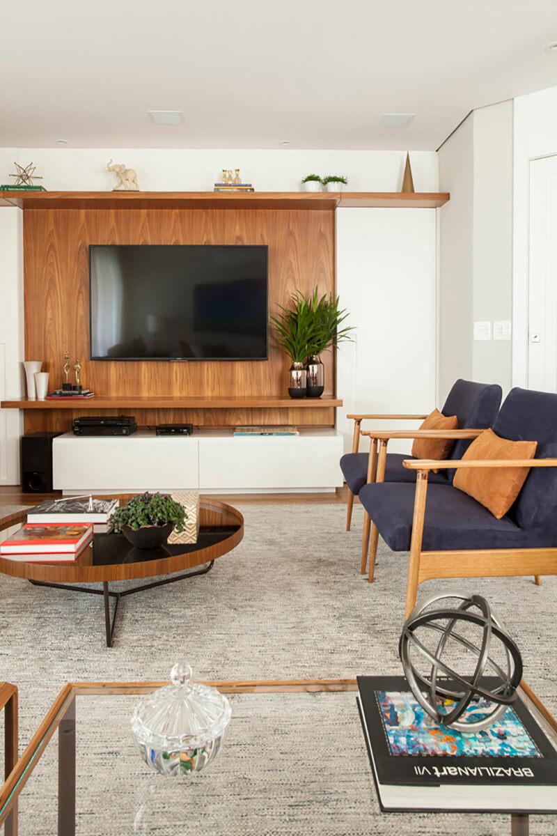sala em tons de azul e terra,painel de madeira, mesa de centro redonda com espelho bronze.