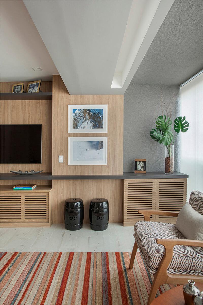 ponto de integraçao de sala e varanda com marcenaria revestindo a parede crianso um canto para adega oculta no armário