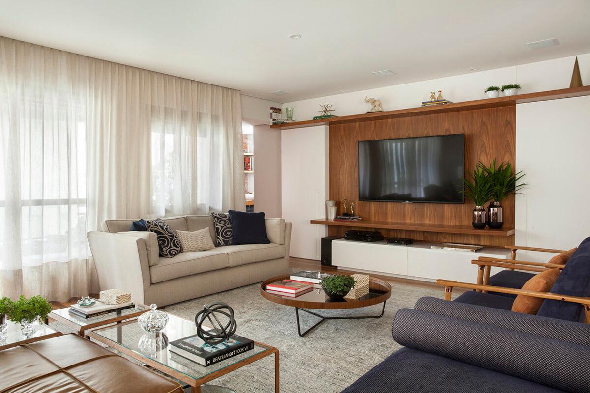 sala integrada em tons de azul e terra, painel em madeira para TV e portas que ocultam a passagem para o área íntima da casa e a cristaleira.