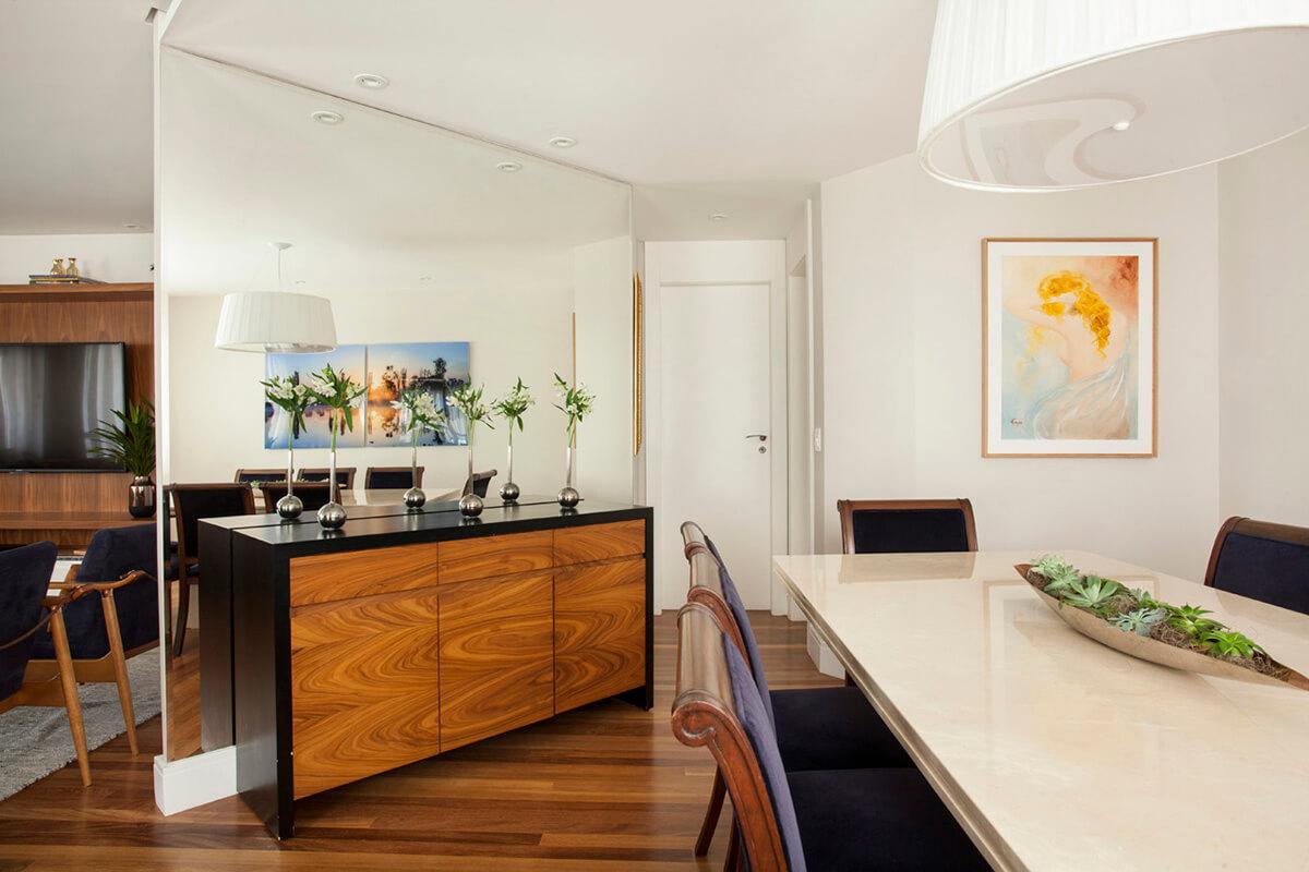 sala de jantar com parede revestida em espelho e buffet emlaca preta e madeira